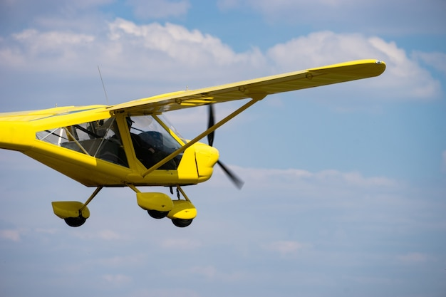 Small yellow private aircraft flying in a blue sky.