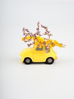 Маленькая желтая игрушечная машинка с букетом полевых цветов на белом фоне.
