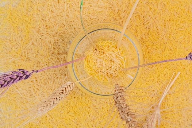 Piccoli vermicelli gialli con vaso di grani.
