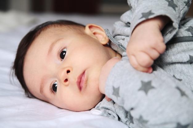 白い部屋のベッドの上でsmallう小さな赤ちゃん。彼の顔の興味と不思議に。ヨーロッパ人。赤ちゃんは驚いた。