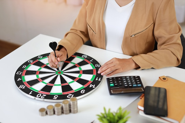 Smart and active asian businesswoman hands putting dart to target dartboard with saving growth on stacking coin on table