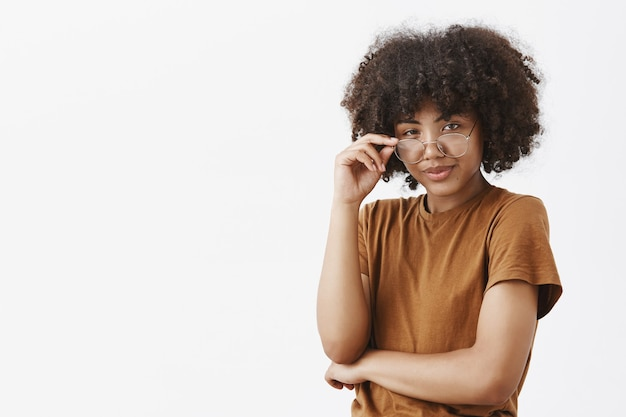 Smart african american female genius with afro hairstyle in trendy brown t-shirt looking from under glasses with knowing look being suspicious smirking as if having great plan