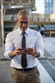 넥타이와 안경을 가진 똑똑한 미국 50 대 사업가 사업 계획 또는 회의 일정 확인