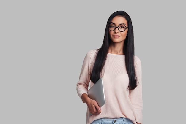 Шикарно и красиво. привлекательная молодая женщина улыбается и смотрит в камеру, стоя на сером фоне