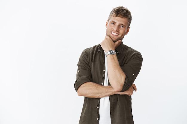 Умный и веселый симпатичный парень с белой идеальной улыбкой, держащий руку на линии подбородка и улыбающийся от удовлетворения и радости, позирует счастливым на фоне серой стены, дружелюбный и расслабленный