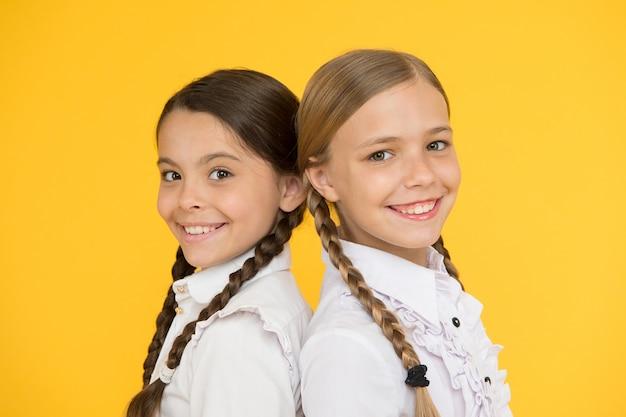スマートで賢い。子供のフォーマルなファッション。海外での教育。かっこいい子供たち。学校の友達。制服を着た幸せな子供たち。黄色の背景に小さな女の子。友情と姉妹関係。親友。