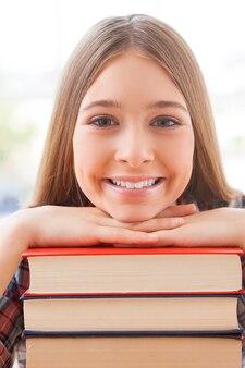 Умный и уверенный. веселая девочка-подросток, опираясь на стопку книг и улыбаясь
