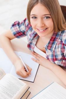 Умная и уверенная в себе школьница. вид сверху веселой девочки-подростка, занимающейся, сидя за столом
