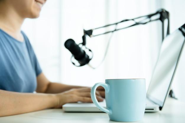 家のオンラインポッドキャストをしているスマートで格好良い若いアジアの女性。オンラインポッドキャストのポッドキャストをラップトップコンピューターとタブレットでライブ録音している実業家。現代の働くライフスタイル