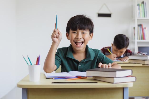 Умный и счастливый азиатский мальчик начальной школы учится в классе