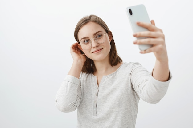 Умная и нежная женщина в очках, откидывающая прядь волос за ухом и мило улыбаясь, делая селфи на новеньком смартфоне, позирует над серой стеной, довольная, делая пост в социальной сети
