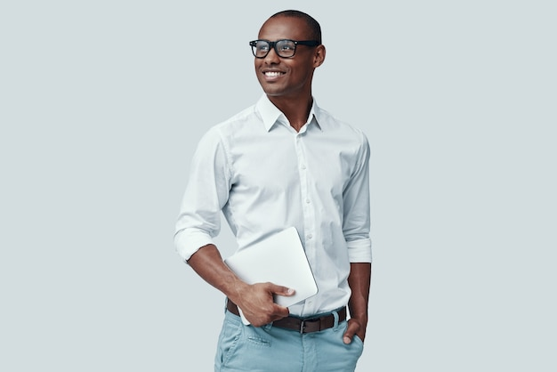 Умный и молодой. красивый молодой африканский человек с помощью цифрового планшета и улыбается, стоя на сером фоне