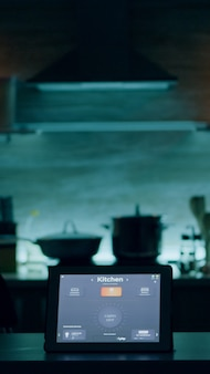 Smart application on tablet placed on kitchen desk in empty house automation system turning on the l...
