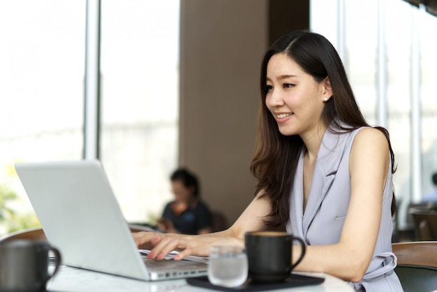 Smart asian beautiful smiling girl working on laptop sitting in coffee shop.