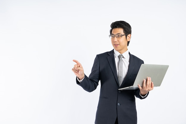 Smart asian businessman holding laptop and point copyspace  for key words against white wall