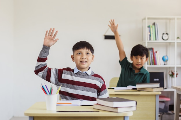 Smart asian elementary students rising their hand in the class for answering teacher question