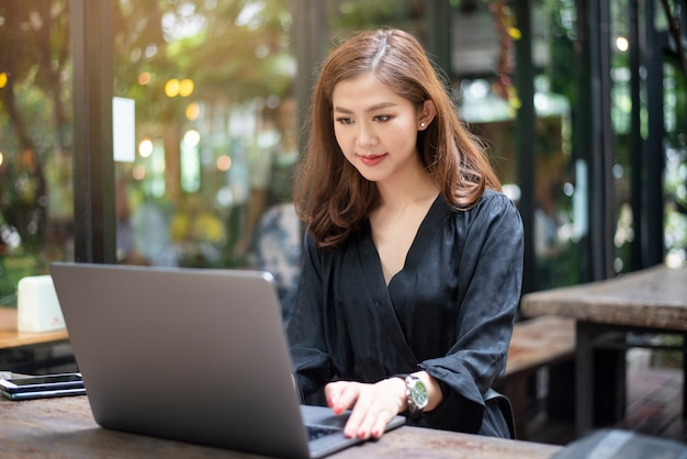 Smart asian female is working with laptop computer