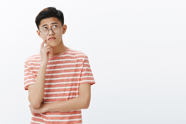 Smart asian guy solving puzzle in mind looking thoughtful and relaxed at upper right corner, thinking, making assumptions touching cheek while making up plan or decision