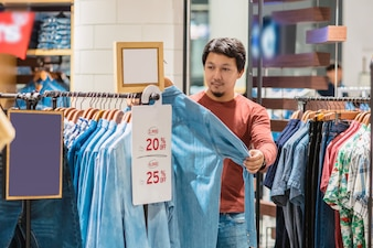 Smart asian man with beard choosing clothes in clothing store at shopping center