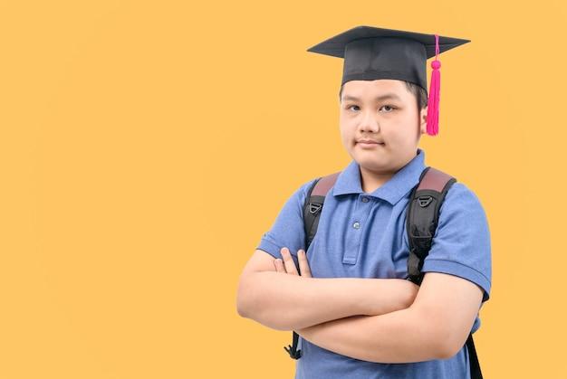 スマートなアジアの学生は卒業帽と交差した腕を着用します