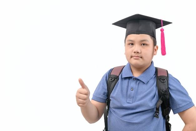 スマートなアジアの学生は卒業帽を着用し、親指を上に表示し、白で隔離のカメラを見て
