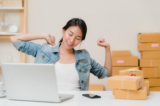 Умный азиатский молодой предприниматель бизнес-леди мсп работает и расслабиться поднять руку вверх и закрыть глаза перед ноутбуком на столе у себя дома.