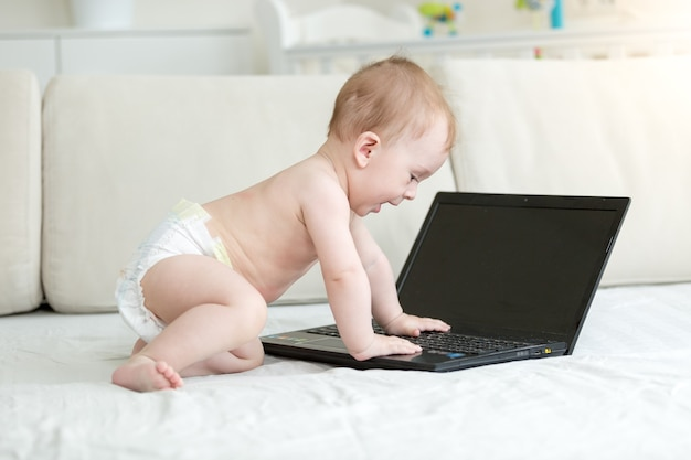 Smart baby in diapers sitting on bed and using laptop