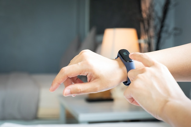 Smart band, women touching fitness smart band on her hand