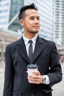 街でコーヒーカップを持ってスーツとネクタイを身に着けているスマートなひげのビジネスマン-選択的な焦点