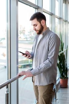 スマートなひげ白人男性は、パノラマの窓の近くのガラスのバルコニーにある都会のモダンなコワーキングオフィスでスマートフォンでテキストメッセージをチャットしています。