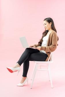 파란색 배경에 격리된 노트북 컴퓨터를 사용하는 똑똑한 아름다운 소녀