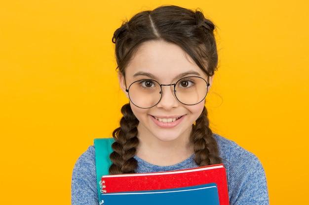 똑똑한 아름다움. 땋은 노란색 배경에 행복 한 소녀입니다. 헤어 살롱. 어린 아이의 아름다움 모습. 안경점. 안경사. 눈 관리. 교정 렌즈. 당신의 아름다움과 시력을 신선하게 유지합니다.