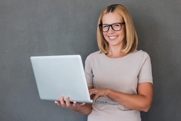 スマートな美しさ。ノートパソコンを持ってカメラを見て笑顔の成熟した女性