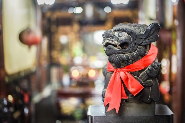 スマートな黒い石のライオン像が右側に見え、赤いスカーフと背景がぼやけています