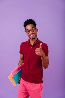 Smart black student posing with thumb up. indoor photo of pleased african guy with books having fun after exams.