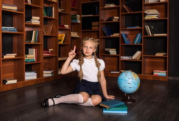 学校の制服を着たスマートブロンドの女の子が地球とクラスの本を上向き