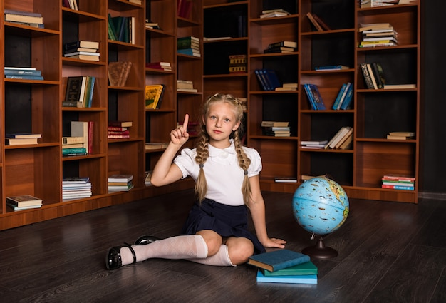 Smart blonde girl in school uniform points up with a globe and books in class