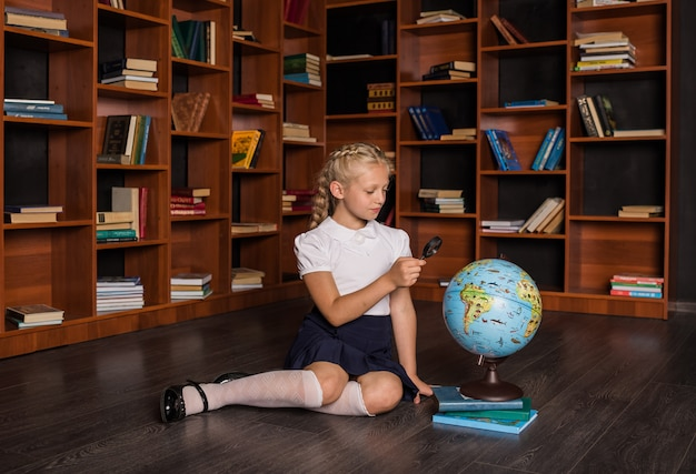 A smart blonde girl in a school uniform sits and studies a globe in the library