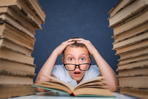 Smart boy in glasses getting crazy of reading book while sitting between two piles of books