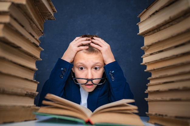 Smart boy in glasses sitting between two piles of books and read book thoughtfully