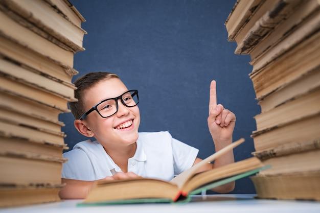 Умный мальчик в очках сидит между двумя стопками книг и смотрит вверх, указывая пальцем.