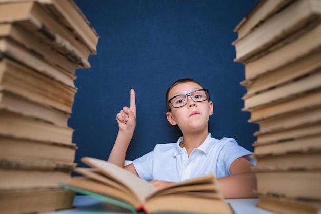 Умный мальчик в очках сидит между двумя стопками книг и смотрит вверх, указывая пальцем