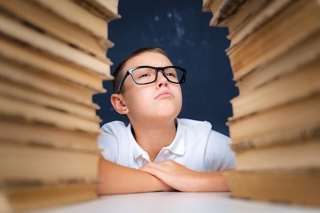 Умный мальчик в очках сидит между двумя стопками книг и смотрит вверх надутыми щеками.