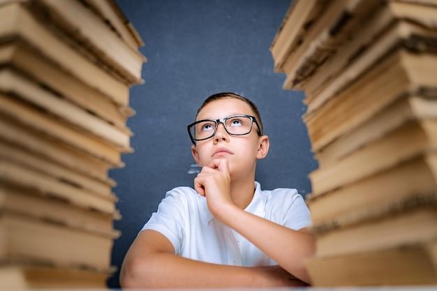 Умный мальчик в очках сидит между двумя стопками книг и задумчиво смотрит вверх.