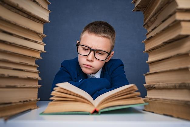 Умный мальчик в очках сидит между двумя стопками книг и задумчиво читает книгу.