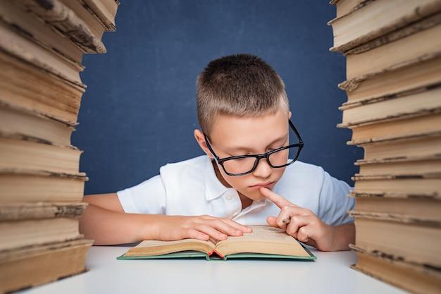 本の2つの山の間に座って思慮深く本を読むメガネのスマートボーイ
