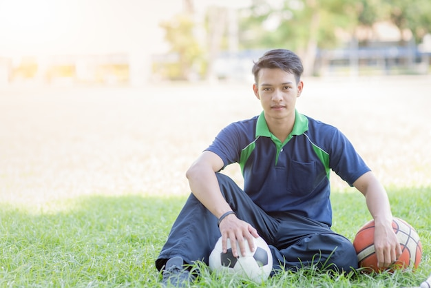 Smart boy sitting with football and basketball on green grass, sport and healthy concept
