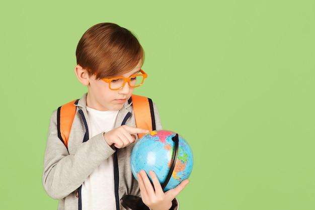 地理を勉強している賢い少年。学校に戻る。地球を見て笑顔の学生。地球を勉強している学校の子供。教育と地理。緑の壁に孤立した男子生徒。