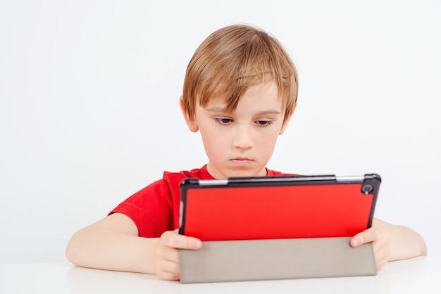온라인 수업 중 가제트를 사용하는 스마트 소년.