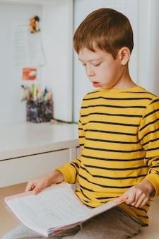 Умный мальчик в очках читает книгу дома